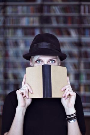 Portrait de femme au chapeau noir avec un livre ouvert, le visage à moitié couvert, cheveux blancs. Hipster fille étudiante dans une bibliothèque Banque d'images