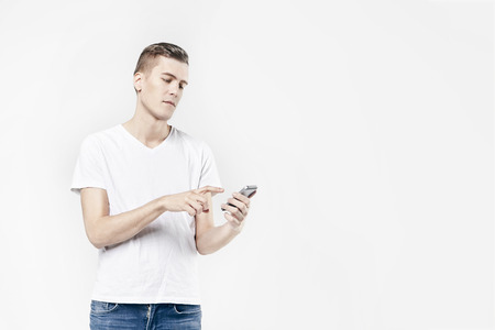 Attractive business man model in white t-shirt isolated on white calling by mobile phone, push buttons hand touching screen. Caucasian skinny hipster guy.