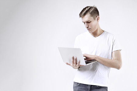 modèle de l'homme d'affaires attrayant en t-shirt blanc isolé sur blanc travail sur ordinateur portable. Penser au visage grave.