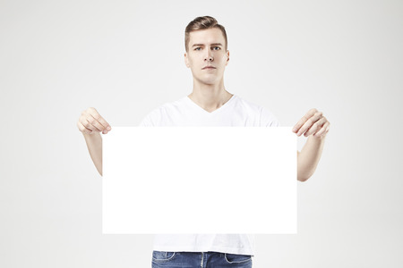 Handsome man model standing with blank big poster or sheet in hands, isolated on white background, wearing jeans and t-shirt