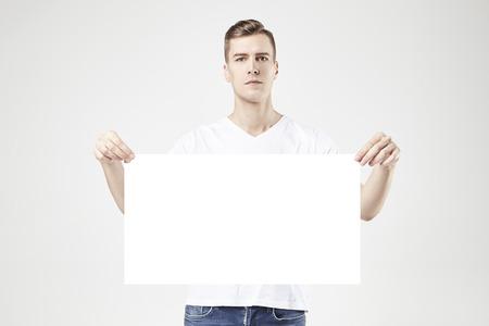 modèle Handsome homme debout avec une grande affiche ou feuille dans les mains vide, isolé sur fond blanc, portant des jeans et t-shirt