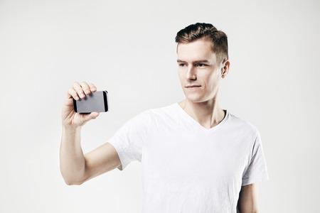 Beau jeune homme prenant une photo par téléphone mobile, isolé sur fond blanc, portant t-shirt blanc Banque d'images