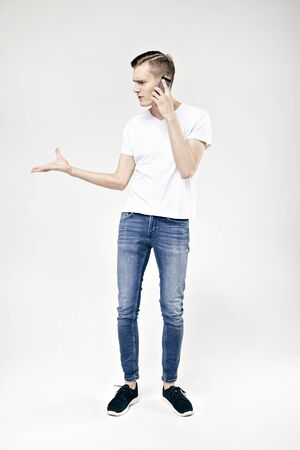 Handsome hipster guy full-length standing talking by phone and swears, isolated on white background, wearing jeans and t-shirt