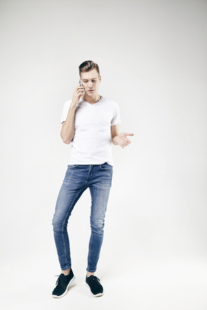 Man model talking by mobile phone wearing jeans and white t-shirt, full-length standing and showing something by left hand