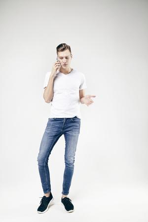 Modèle homme parlant par téléphone portant des jeans mobiles et t-shirt blanc, pleine longueur debout et montrant quelque chose à la main gauche Banque d'images