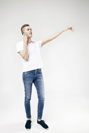 Handsome guy full-length standing and showing something by outstretched arm, using mobile phone, isolated on white background, wearing jeans and t-shirt Stock Photo