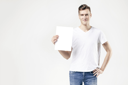 Handsome guy standing with blank sheet in hand, isolated on white background, wearing jeans and t-shirt. Free available space for layout text