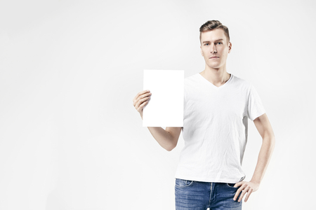 Hipster man model standing with blank sheet in hands, isolated on white background, wearing jeans and t-shirt. Space for design layout.