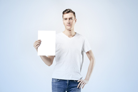 homme modèle Hipster debout avec une feuille vierge dans les mains, isolé sur fond blanc, portant des jeans et t-shirt. Espace pour la conception mise en page. Banque d'images