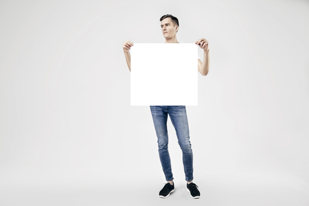 Handsome guy full-length standing with blank big poster or sheet in hands, isolated on white background, wearing jeans and t-shirt Archivio Fotografico