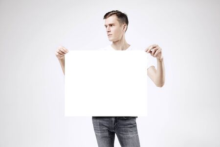 Handsome guy standing with blank big poster or sheet in hands, isolated on white background, wearing jeans and t-shirt
