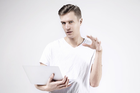 Attractive business man model in white t-shirt isolated on white working with laptop, showing something by  left hand. Caucasian skinny hipster guy. Banque d'images