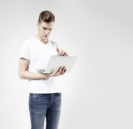 Young hipster business man in white t-shirt standing with laptop in hands. Full body, wearing jeans, isolated on white
