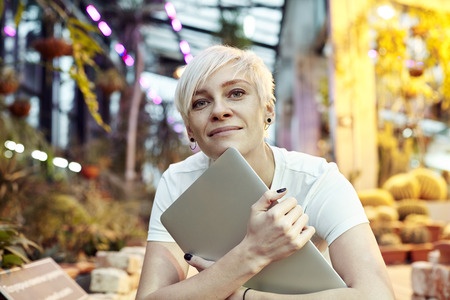 Beautiful hipster woman sitting in park or botanical garden, pensive look, smiling, thinking about things. Holding closet laptop. Archivio Fotografico