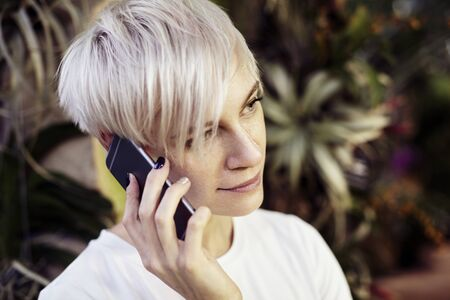 Portrait of hipster caucasian woman with blonde short hair talking by mobile phone. Smiling half-face face, Indoor botanical garden interior