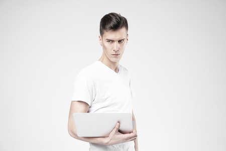 Handsome hipster style business man model with modern laptop in hands, wearing white t-shirt. Isolated on white background in studio.
