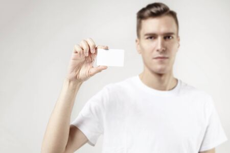 Portrait of attractive businessman holding blank business card, empty space for layout, with white background. Focus on card.