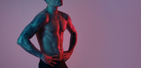 Fashion portrait of sport fit attractive man. Masculine naked torso tattooed hands. Color flash studio light.
