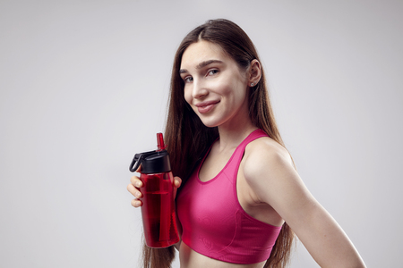 Portrait of young sporty caucasian woman wearing fitness top with bottle of water