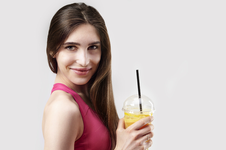 Portrait of sporty young caucasian woman holding plastic glass of orange juice