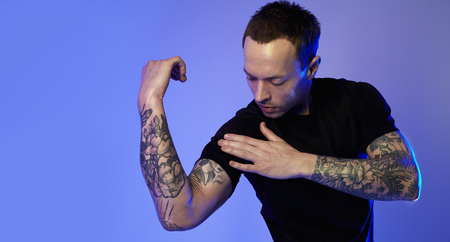 Portrait of sporty fitness man showing muscular triceps, tattooed hands, hipster. Color flash studio light