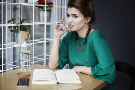 Beautiful young woman wearing green drinking pure water in cafe, having breakfast, opened book spread on table