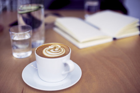 Cup of coffee cappucino, glass of pure water, bottle on wooden table, bright interior daylight Archivio Fotografico
