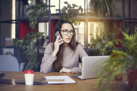 Beautiful girl wearing eye glasses in coworking studio talking by smartphone. Concept of young people working with mobile gadgets. Modern office blurred on background. Horizontal Banque d'images