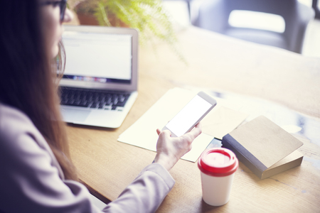 Businesswoman using phone and laptop while sitting in his modern loft office. Concept of young people working mobile devices. Blurred background, day light