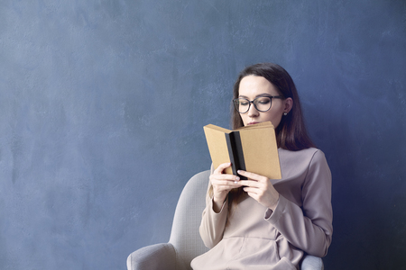 collegue: Beautiful businesswoman sitting in loft office reading vintage book. Look into opened book brown cover. Dark blue wall background, day light