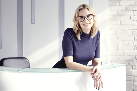 Beautiful blonde friendly woman behind the reception desk, meet and smiling. Sunshine in modern office. Business conception working people Banque d'images