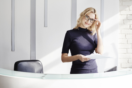 portative: Beautiful blonde friendly woman behind the reception desk, administrator talking by phone. Sunshine in modern office. Business conception working people Stock Photo