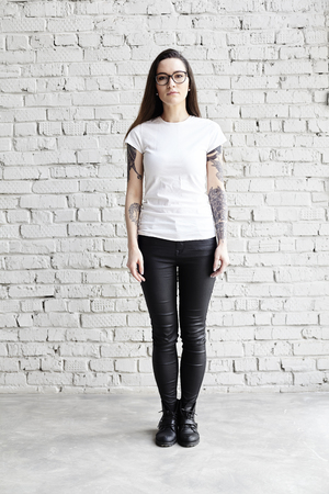 Young tattooed woman wearing blank t-shirt, standing in front of brick wall in loft