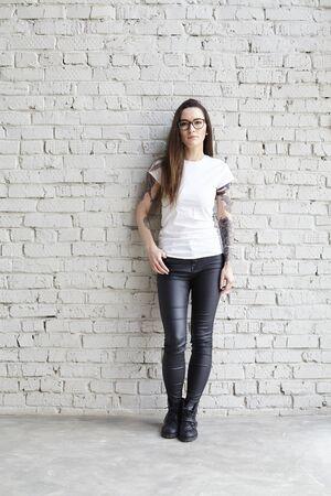 Jeune femme tatouée portant t-shirt blanc, debout devant le mur de briques dans le loft