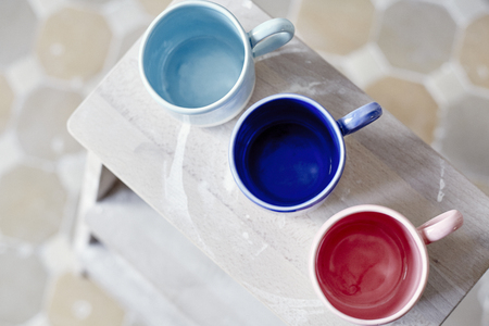 Samples handmade ceramic colored cups on wooden table, working process in studio
