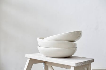 Samples handmade ceramic white plates on wooden table, working process in studio