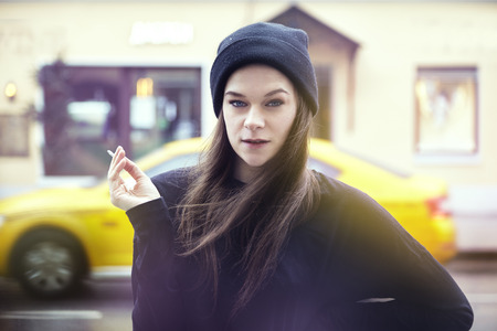 Young pretty woman smoking outside. Hipster outfit, wearing black hat and t-shirt, city yellow taxi on the background