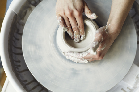 Ceramic working process with clay potters wheel, close-up of woman hands