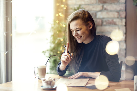 Beautiful young woman laugh drinking coffee in cafe restaurant, portrait of laughing happy lady near window. Vocation holidays evening concept Stock Photo