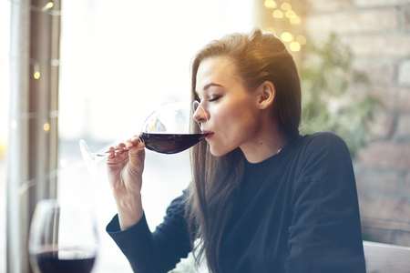 Beautiful young woman drinking red wine with friends in cafe, portrait with wine glass near window. Vocation holidays evening concept Banque d'images