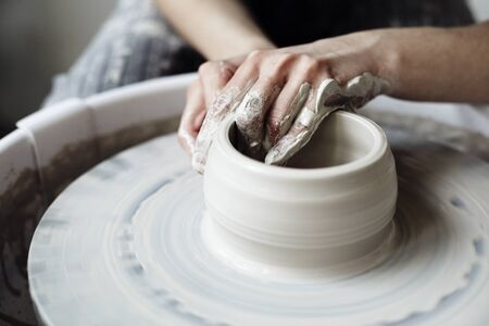 The womans hands close up, the masterful studio of ceramics works with clay on a potters wheel