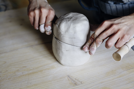 Woman hands close-up, forming crude clay in a potters workshop studio. Craft-work