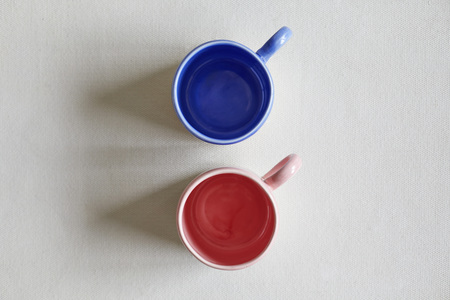 blue and red ceramic hand-crafted cups stand on a white table, view from above Stock Photo