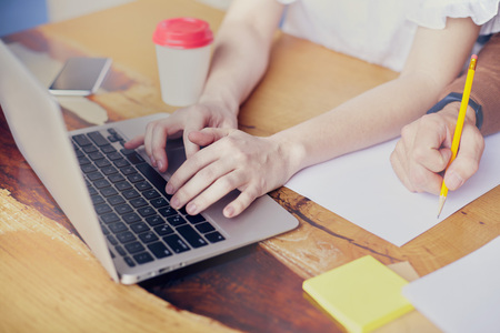 Business meeting in modern office, close-up of woman hands on keyboard laptop on wooden table, man hand writing by pencil