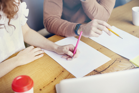 Business Student meeting in office, close-up of woman man hands writing on paper sheet, empty space for layout. Stationary on wooden table.