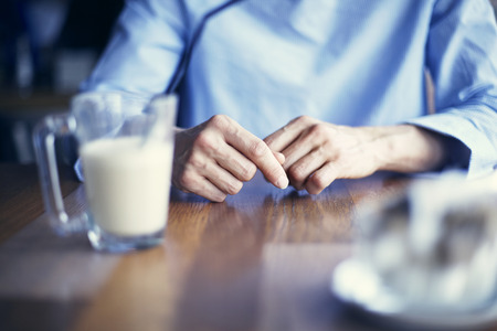 Woman hands close-up, lady wearing blue shirt having coffee in cafe or restaurant alone, loneliness Stock Photo