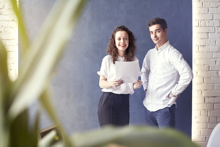 Two young professionals or students woman man happy with business meeting, smiling and talking about project. Office blue wall background