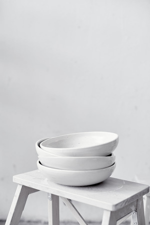 White empty ceramic plates stand in a pile stand on a wooden stool, kitchen equipment