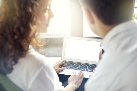 Young business partners are working together, using laptop in office, blank screen computer for layout close-up