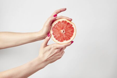 Juicy grapefruit in beautiful womans hands isolated on white